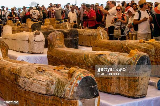 Tourists photograph sarcophagi displayed in front of Hatshepsut Temple in Egypt's valley of the Kings in Luxor on October 19 2019 Egypt revealed...