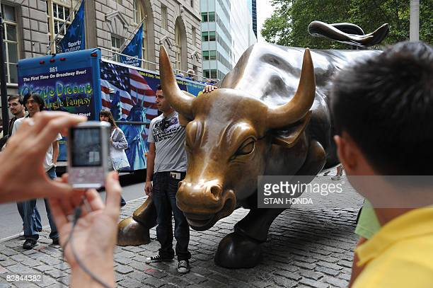 Tourists photograph the bull on lower Broadway near Wall Street September 16 2008 in New York Wall Street saw highly volatile trade Tuesday as...