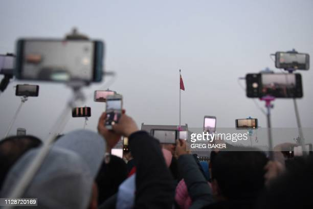 TOPSHOT Tourists photograph the daily flagraising ceremony in Tiananmen Square before the opening session of the National People's Congress in...