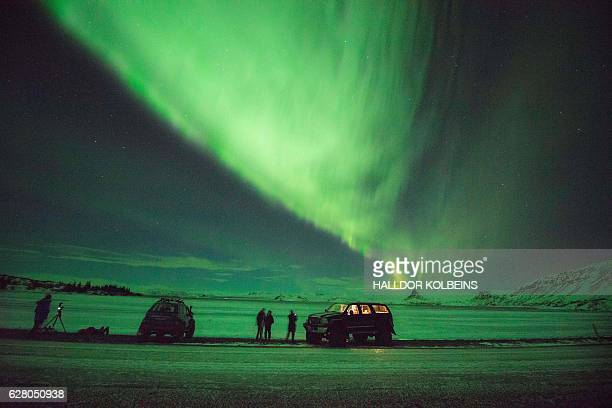 Tourists photograph the Northern Lights at lake Thingvellir Iceland on January 13 2016 An island of ice and lava battered by the Arctic winds...