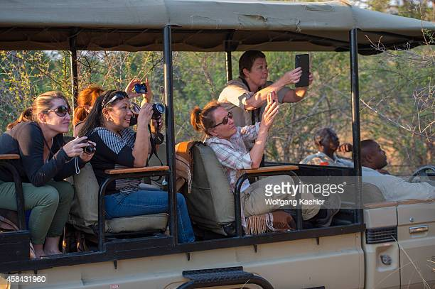 Tourists photographing a leopard with iPads and iPhones in South Luangwa National Park in eastern Zambia
