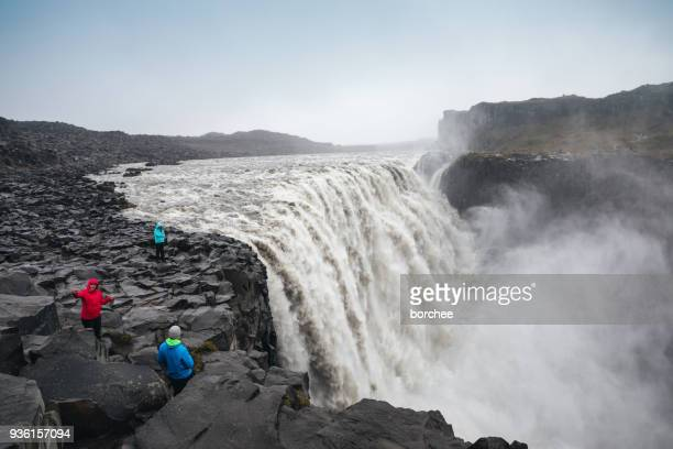 tourists photographing dettifoss in iceland - dettifoss waterfall stock photos and pictures
