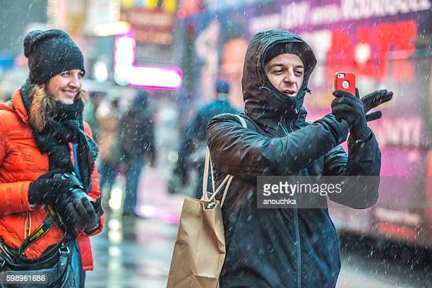 Tourists photographing New York under snow, USA