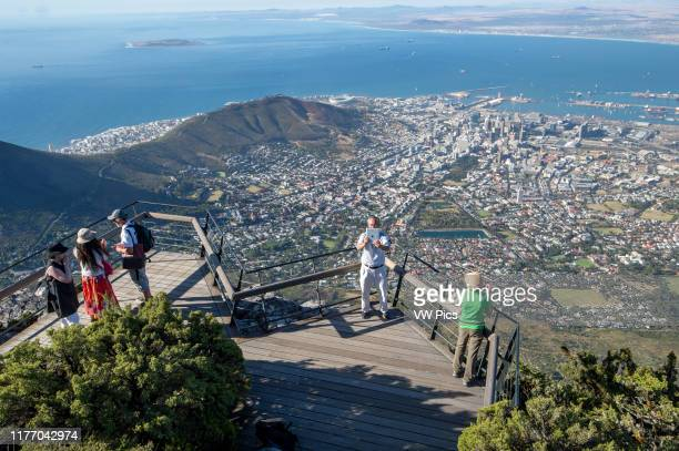 Tourists photographing the City Bowl of Cape Town, South Africa. Seen from the top of Table Mountain.