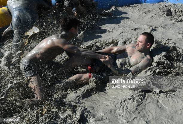 Tourists play in a mud pool during the 21th Boryeong Mud Festival at Daecheon beach in Boryeong on July 14 2018 The annual festival which runs from...