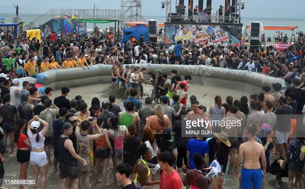 Tourists play in a mud pool during the 22th Boryeong Mud Festival at Daecheon beach in Boryeong on July 20 2019 The annual festival which runs from...