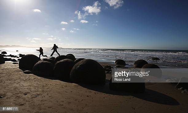 Tourists play in the Moeraki Boulders on July 10 2008 in Dunedin New Zealand Much of Dunedin was covered by frost after overnight temperatures...