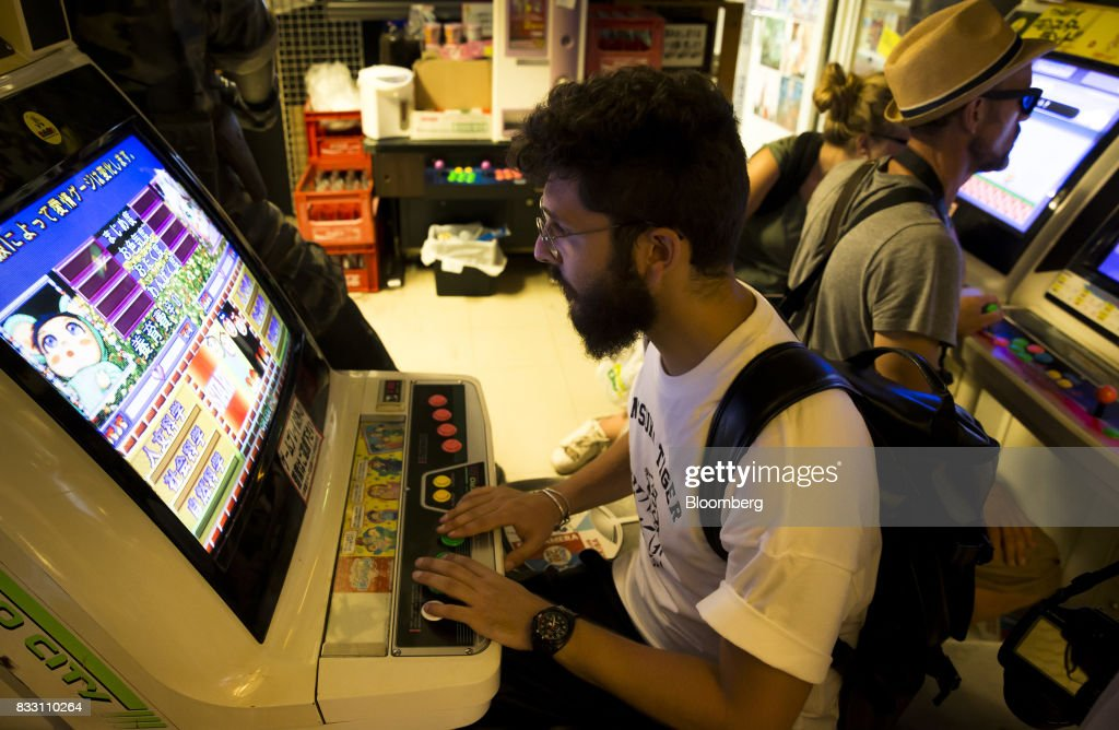 Tourists play on arcade video game machines inside the Super Potato video game store in the Akihabara district of Tokyo, Japan, on Tuesday, Aug. 8, 2017. Renewed interest in vintage Japanese videogamesis drawing buyers to the country'sonline markets and retro gaming shops. Photographer: Tomohiro Ohsumi/Bloomberg via Getty Images