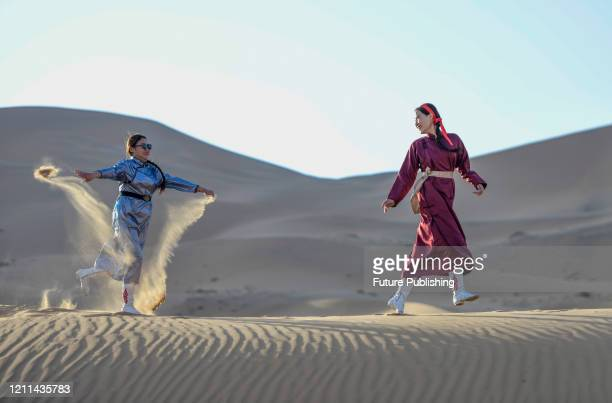 Tourists play on the sand mountain of Badain Jilin desert Geopark. Inner Mongolia, China, May 1, 2020.- PHOTOGRAPH BY Costfoto / Barcroft Studios /...
