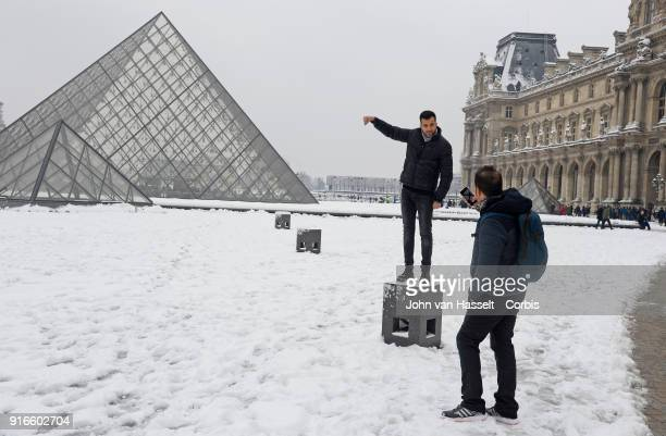 Tourists play perspective with their smartphone at the Pyramid deuLouvre on February 07 2018 in Paris France After a steady snowfall the French...