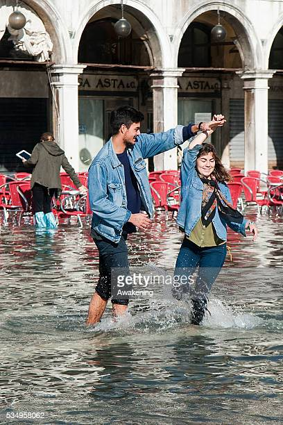 Tourists play with water on the flooded Piazza San Marco on November 5 2013 in Venice ItalyThe high tide or acqua alta as it is locally known stood...