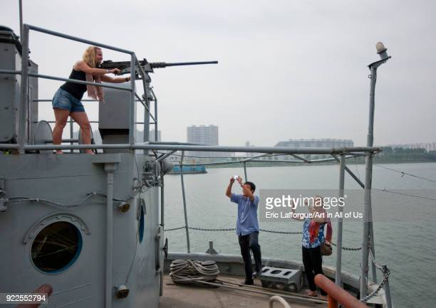 Tourists playing with machine gun on Uss Pueblo american spy ship Pyongan Province Pyongyang North Korea on September 10 2011 in Pyongyang North Korea