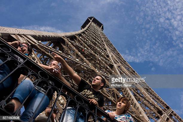 Tourists point out landmarks and admire Paris below from the second level of the Eiffel Tower. With the girders of the tower rising above their heads...