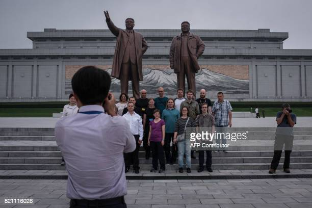 Tourists pose for a group photo before statues of late North Korean leaders Kim IlSung and Kim JongIl on Mansu hill in Pyongyang on July 23 2017 The...