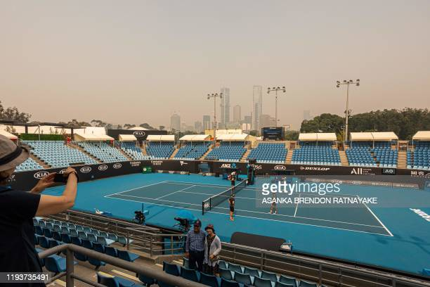 TOPSHOT Tourists pose for a photo in the stands of one of the outside courts at Melbourne Park as the horizon is covered with thick smoke haze in...