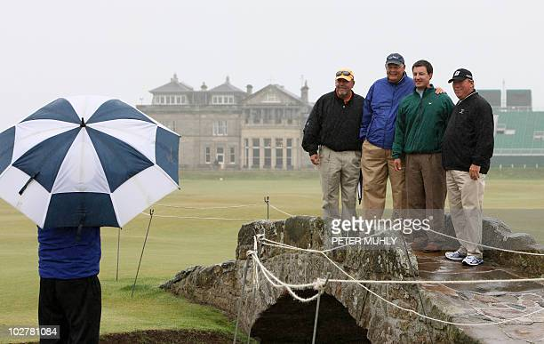 US tourists pose for a photo on the Swilcan Bridge with the the RA Clubhouse behind on July 10 2010 near the 18th green ahead of the 2010 Open...