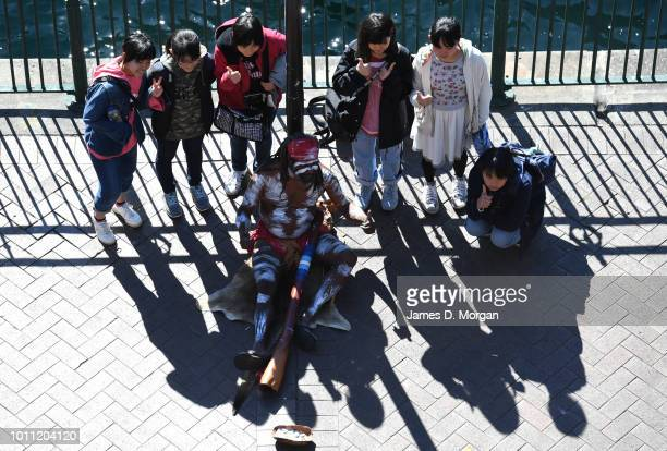 Tourists pose for a photo with an Aboriginal singer at Circular Quay in the warm winter sunshine on August 5 2018 in Sydney Australia Sydney has had...