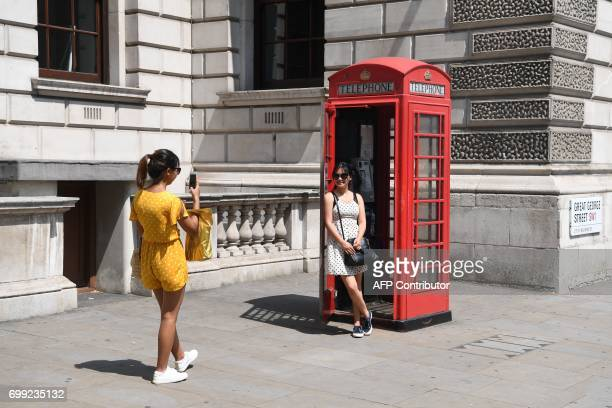 Tourists pose for a photograph in a Telephone Box in the hot weather in central London on June 21 2017 Europe sizzled under a continentwide heatwave...