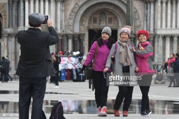 Tourists pose for a picture at Piazza San Marco in Venice on January 19 2018 / AFP PHOTO / Andrea PATTARO