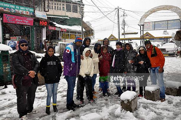 Tourists pose for a picture during snowfall near Gandhi Chowk on January 14 2015 in Dalhousie India Shimla and its surrounding resorts of Kufri Fagu...