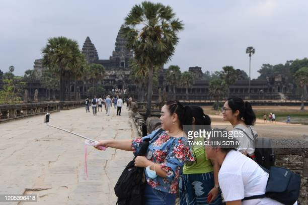 Tourists pose for a selfie during their visit to the Angkor Wat temple in Siem Reap province on March 6, 2020. - The deadly COVID-19 novel...