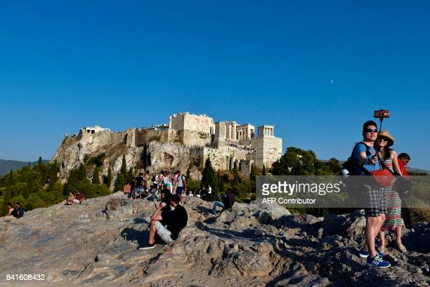 Tourists pose for a 'selfie' on Areopagus Hill in front of the Acropolis in Athens on September 1 2017 / AFP PHOTO / LOUISA GOULIAMAKI