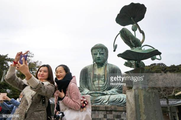 Tourists pose for a selfie photograph in front of the Great Buddha at the Kotokuin temple in Kamakura Kanagawa Japan on Monday Feb 19 2018 The Japan...