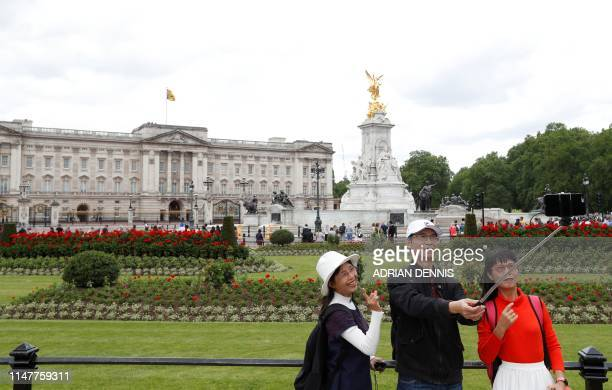 Tourists pose for a 'selfie' photograph outside Buckingham Palace in central London on June 3 on the first day of the US president and First Lady's...
