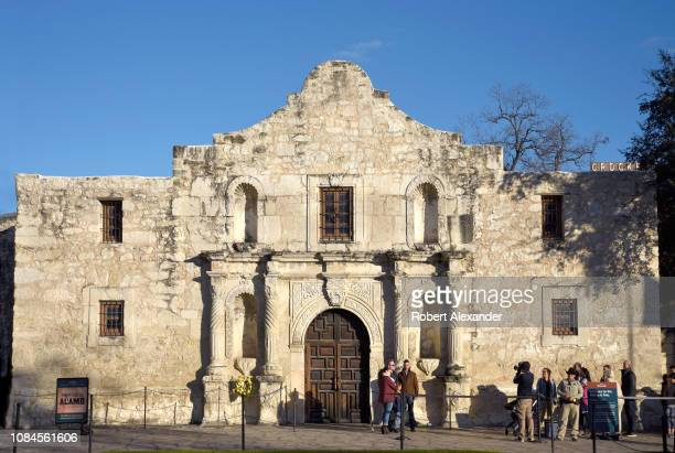 Tourists pose for a souvenir photograph in front of Mission San Antonio de Valero better known as The Alamo The former Franciscan mission was the...