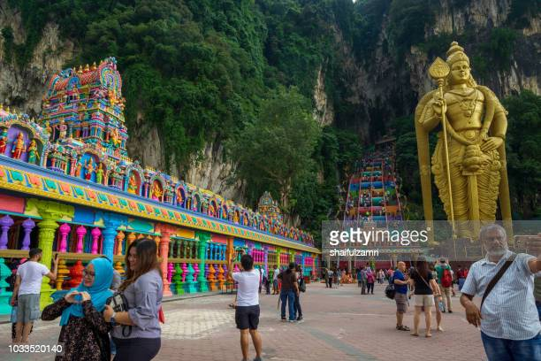 Tourists pose for camera at front of Batu Cave temple, guarded by a monumental statue of Hindu deity Lord Murugan, an iconic and popular tourist attraction and worshippers.