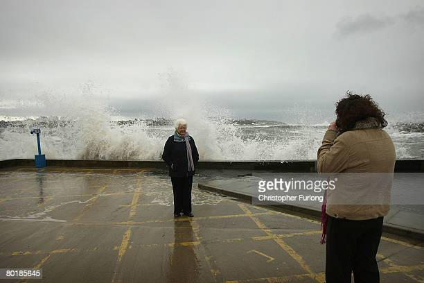 Tourists pose for photographs as waves lash the sea wall at Trearddur at high tide on March 10 near Holyhead Wales Weather forecasters are saying...