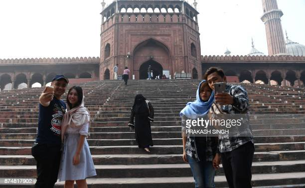 Tourists pose for photographs outside Jama Masjid amid heavy smog in the Indian capital New Delhi on November 16 2017 Delhi is now the world's most...