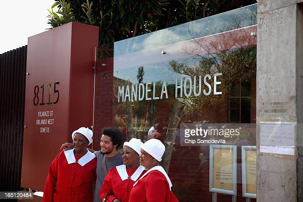 Tourists pose for photographs outside the Mandela House and Museum on historic Vilakazi Street in Soweto March 31 2013 in Johannesburg South Africa...