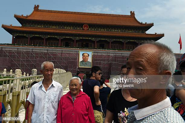 Tourists pose for photos in Tiananmen Square in front of scaffolding next to the portrait of late communist leader Mao Zedong on Tiananmen rostrum in...