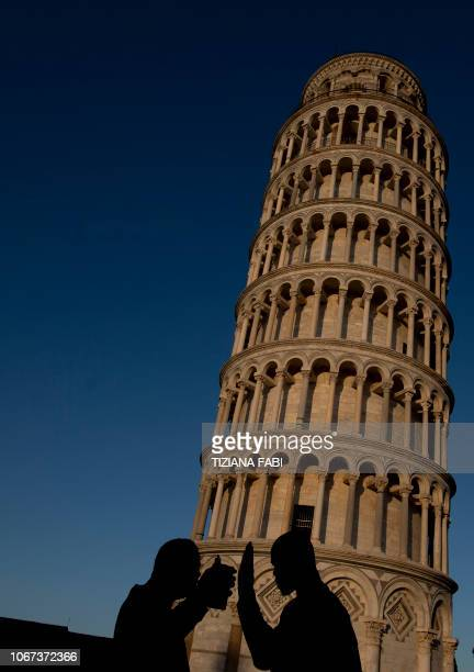 Tourists pose for photos with the Pisa Tower in background in Pisa on November 28 2018 The Leaning Tower of Pisa is now stable and has even...