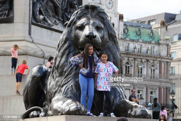 Tourists pose for pics next to a sculpture during warm weather in Trafalgar Square. Following the relaxation of lockdown measures during Covid-19...