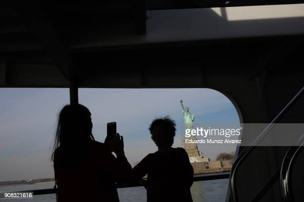 Tourists pose for pictures as the cruise goes around the statue of Liberty on January 21 2018 in New York City The iconic landmark remains closed as...