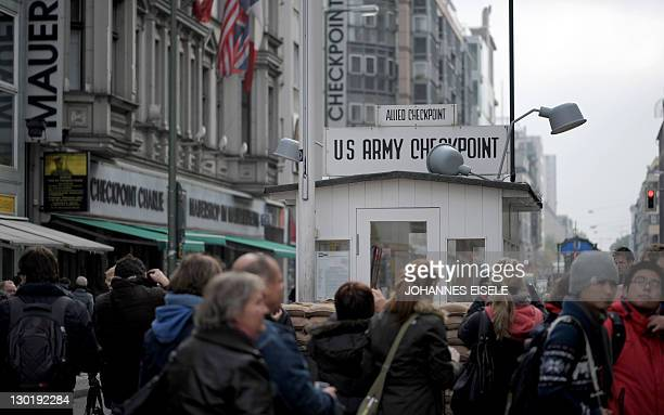 Tourists pose for pictures at the former Allies' checkpoint at Checkpoint Charlie in Berlin on October 24 2011 where a plaque commemorates the 50th...