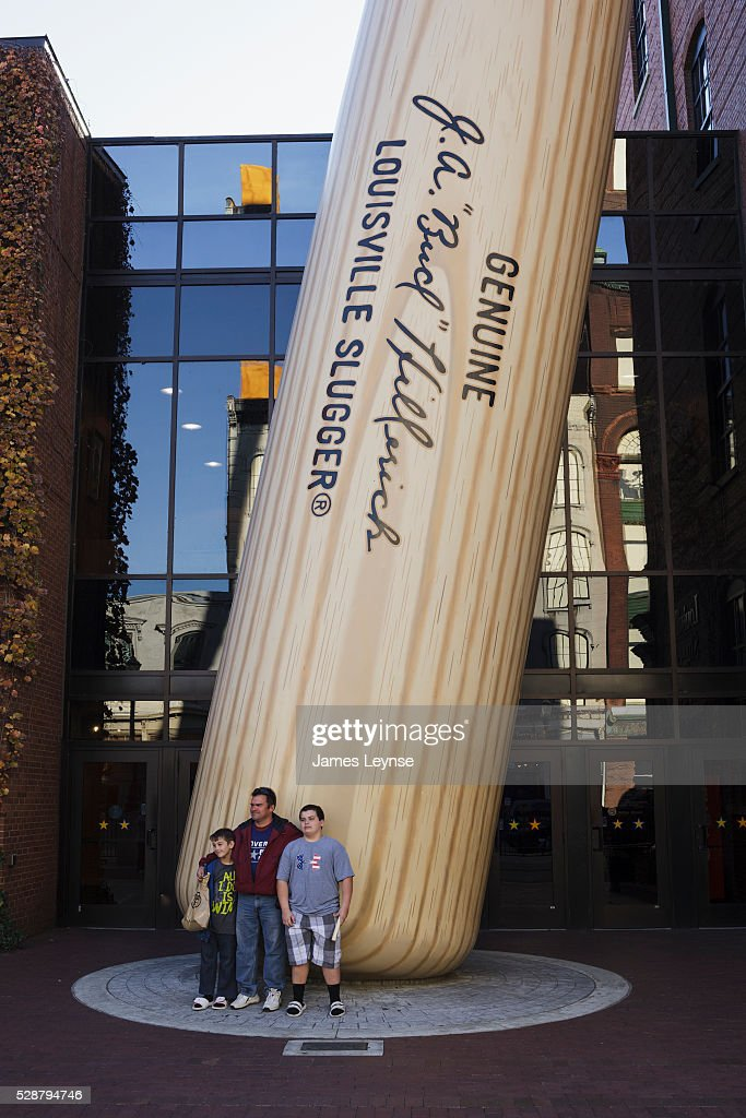Tourists pose for pictures in front of a giant bat outside