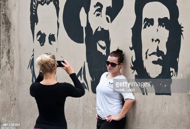 Tourists pose for pictures in front of graffitis of images of revolutionary leaders in Havana on January 7 2015 Last month the United States...