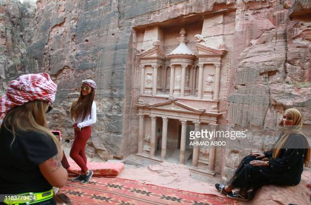 Tourists pose for pictures in front of the ancient Khaznah monument carved in the rock cliff in Jordan's archaeological city of Petra south of the...