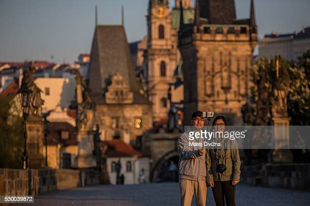 Tourists pose for 'selfie' on the Charles Bridge during a sunrise on May 10 2016 in Prague Czech Republic The Charles Bridge construction began in...