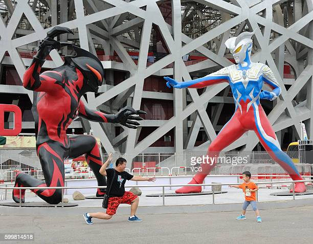 """Tourists pose in front of sculptures of a 5-meter-tall superhero """"Ultraman"""" and a monster Belial beside the National Stadium on September 6, 2016 in..."""