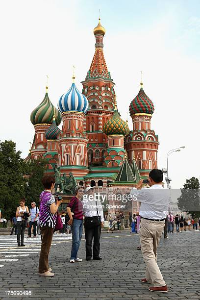Tourists pose in front of St Basil's Cathedral in Red Square ahead of the IAAF World Championships on August 6 2013 in Moscow Russia