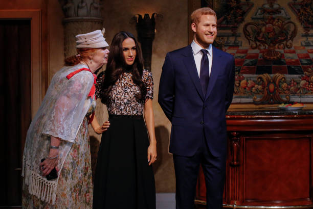 Tourists pose next to wax sculptures of Meghan Markle and Prince Harry as they attend a royal wedding watch party at the Madame Tussauds wax museum...