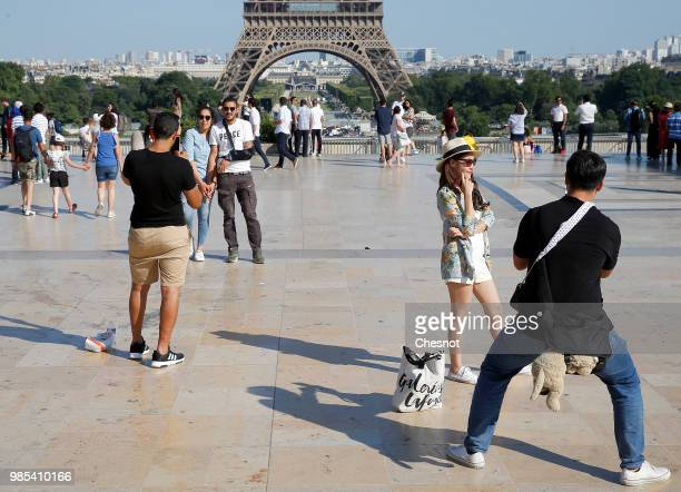 Tourists pose on the Trocadero esplanade in front of the Eiffel Tower on June 27, 2018 in Paris, France. After two dark years following the terrorist...