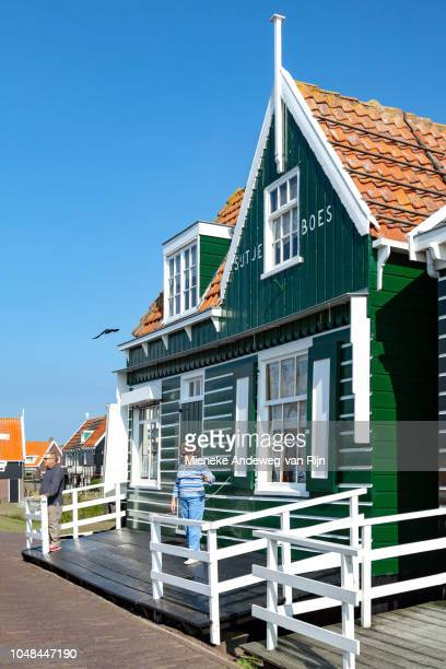 Tourists pose outside the Sijtje Boes cottage, in Marken, North Holland, The Netherlands