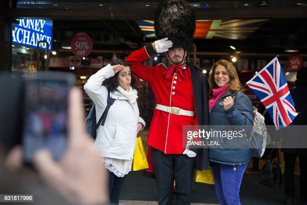 Tourists pose together for a picture with a man in a Guardsman's uniform in central London on January 16 2017 Prime Minister Theresa May won...