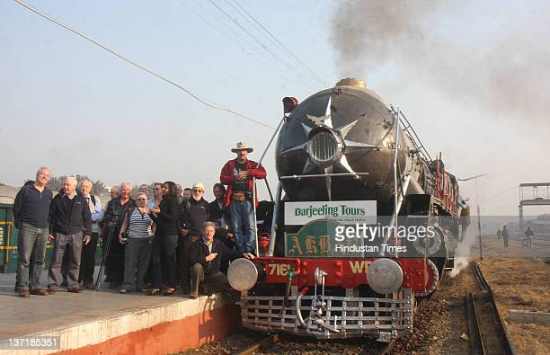 Tourists pose with a special Heritage train powered the steam engine Akbar as it leaves from Delhi Cant station to Alwar on January 14 2012 in New...
