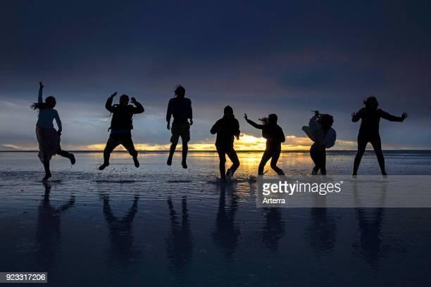 Tourists posing at sunset on the Salar de Uyuni Salar de Tunupa world's largest salt flat Daniel Campos Province in Potosi Bolivia